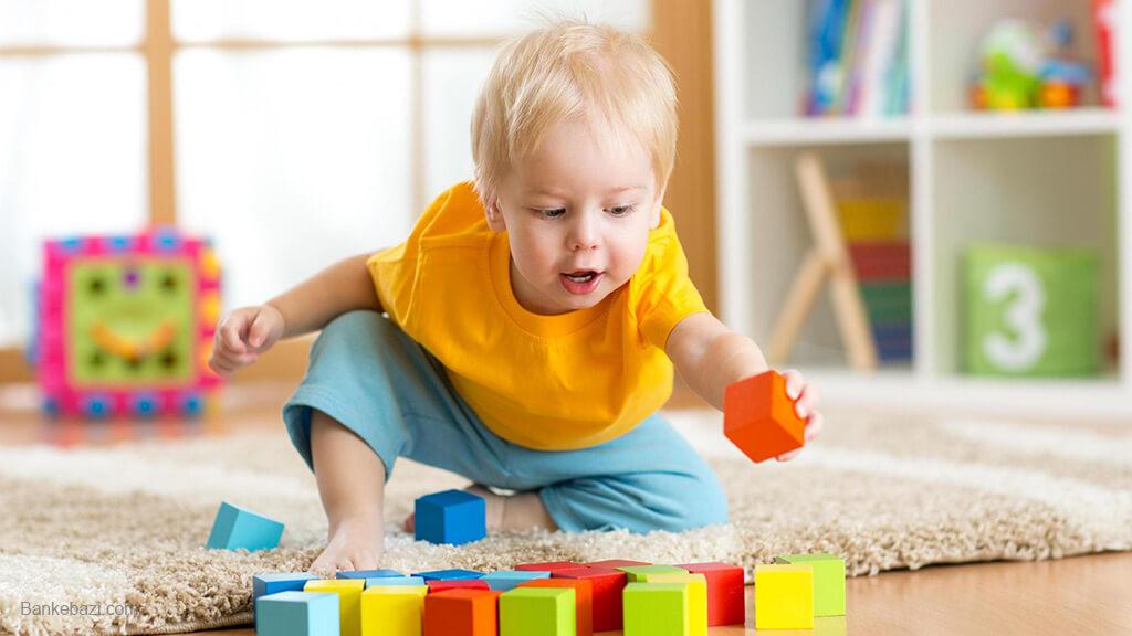 بازی کودک دو ساله با بلوک چوبی